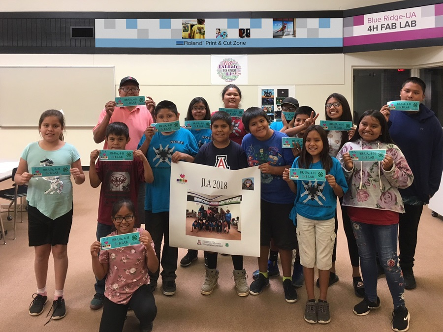 Apache Tribe 4-H Junior Leadership Academy students display bumper stickers made using a Roland wide-format printer/cutter.