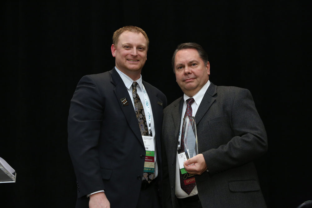 Photo of Roland DGA Manager of Business Development Grant Davis receiving Roland DGA Corporation's NADL 2019 Supplier of the Year Award.