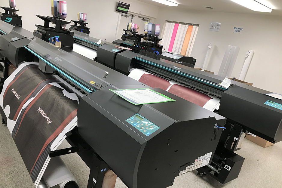 Roland dye-sublimation printers in Savi Customs' production room