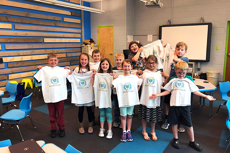 Burrell Elementary students hold the t-shirts they made on the Roland BT-12 direct-to-garment printer