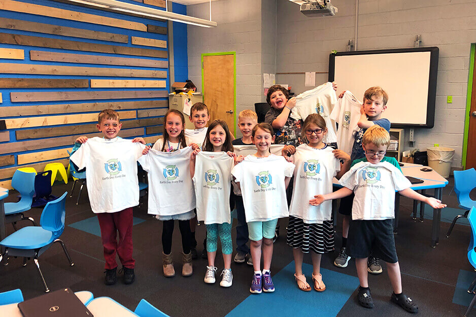 Burrell Elementary students hold the t-shirts they made using the Roland BT-12 direct-to-garment printer