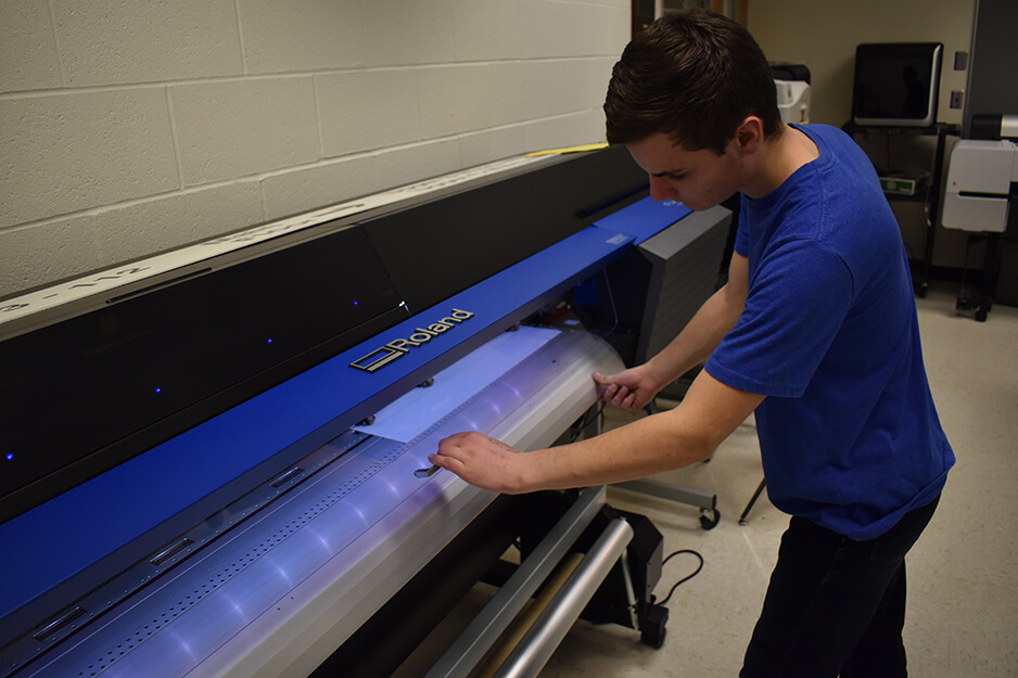 A student at Roseville's student-run print shop adjusts media on the Roland TrueVIS VG2 digital printer/cutter