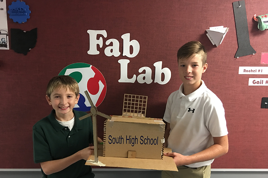 Two students hold a project they built in front of wall graphics for their Fab Lab