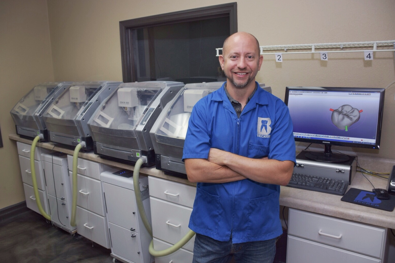 Daniel Becker, C.D.T. with Becker Dental Lab's four Roland DWX-50s