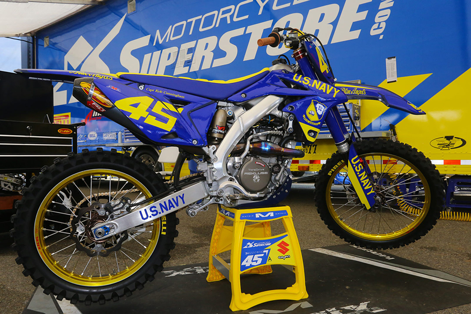 Motocross racing bike with blue and gold graphics against a backdrop of Motocross Super Store banner