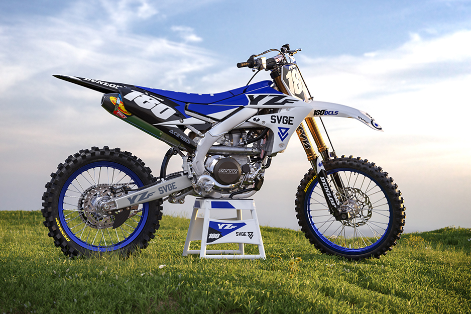 Motocross racing bike with blue and white graphics in a field of grass